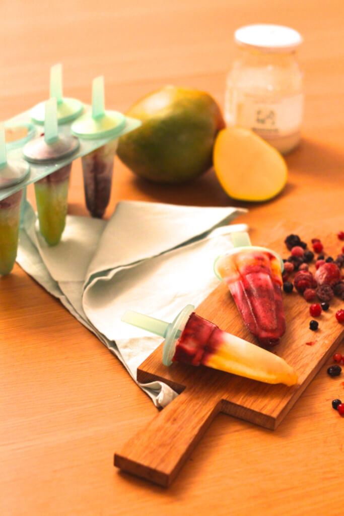 Découvrez ma recette de bâtonnets glacés au yahourt et coulis de fruits rouges et mangue